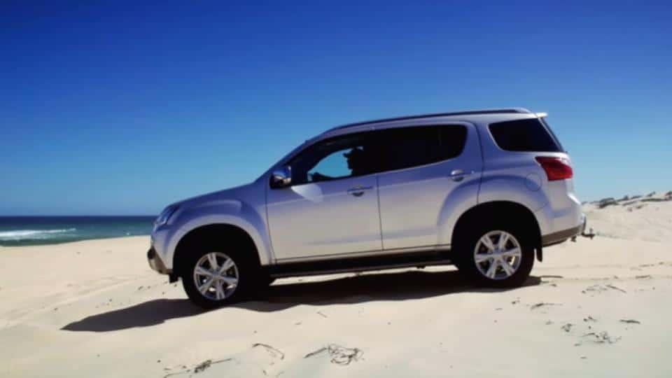 suv driving on a beach sand tracks