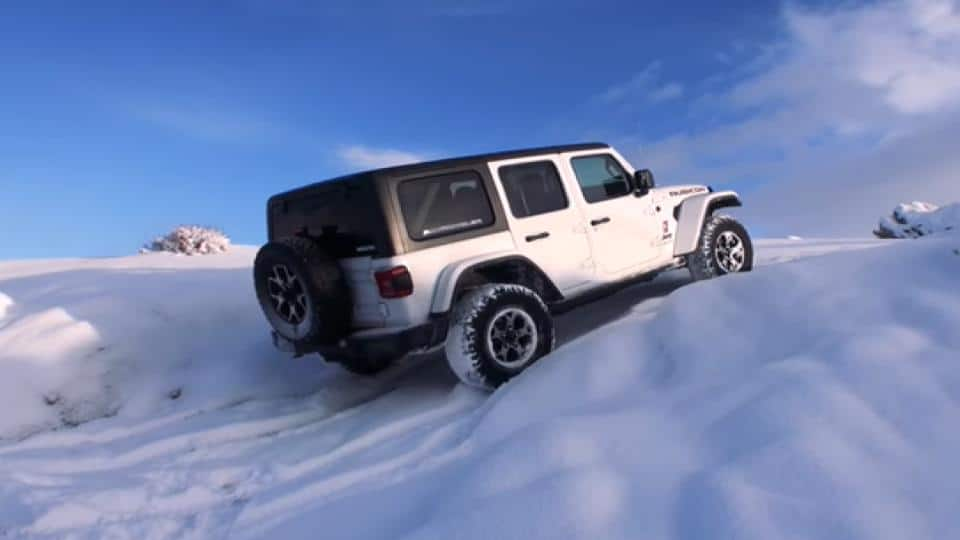 jeep driving in snow on an uphill position